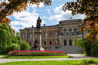Outdoor view of a statue in front of a large red brick building. Photo.