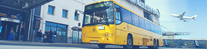 A bright yellow bus parked outside an entrance marked terminal. Photo.