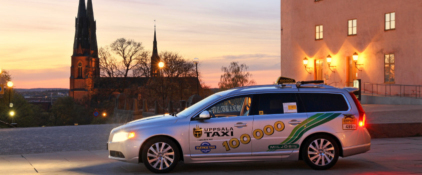 A car marked Uppsala Taxi parked in front of the silhouette of Uppsala Cathedral. Photo.