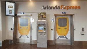 Ticketbox near doors under Arlanda Express sign. Photo.
