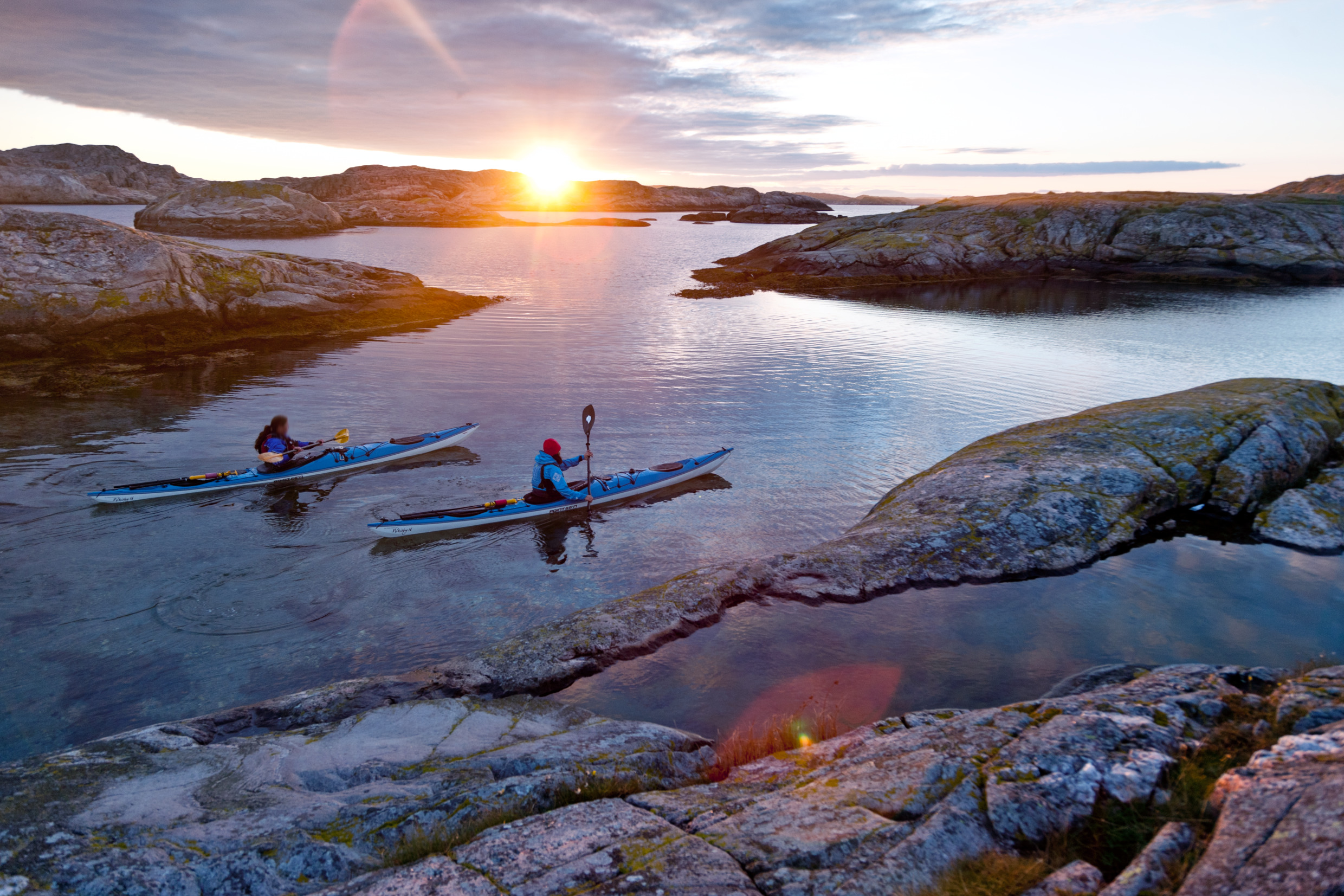 Two persons paddeling kayak in sunset. Photo.